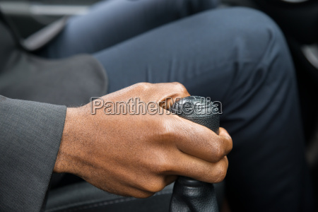 persons hand changing gear while driving