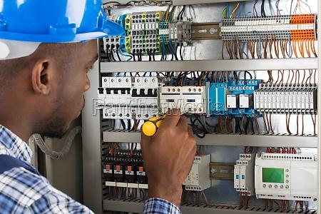 elektriker der fusebox mit schraubenzieher ueberprueft