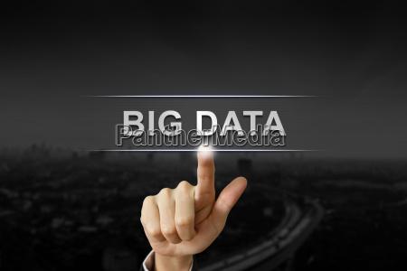 business hand pushing big data button