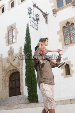 father carrying son looking at map