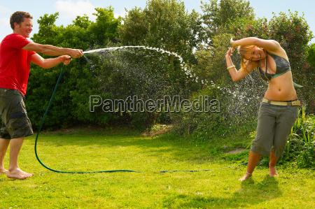 man spraying woman with garden hose