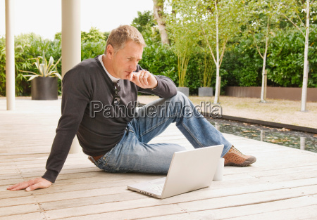 businessman looking at laptop outside