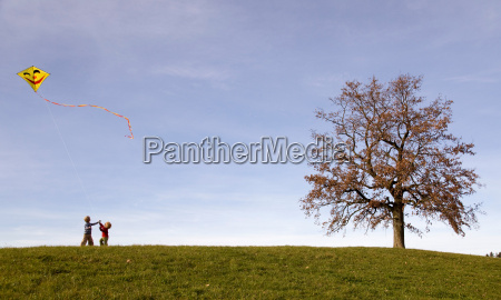 two boys fly a kite