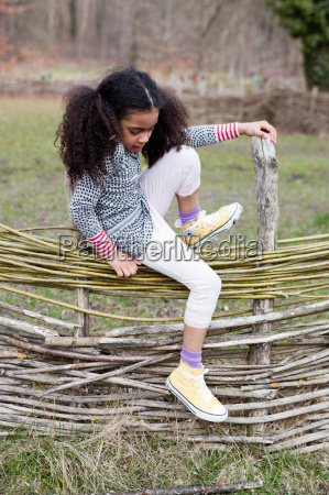 young girl climbing over fence