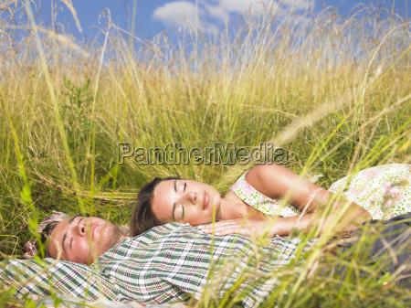 pareja acostada en el campo de