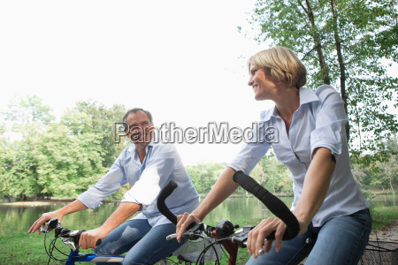 middle aged couple riding bicycles