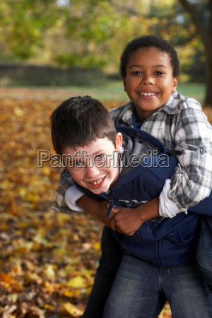 two boys playing in autumn leaves