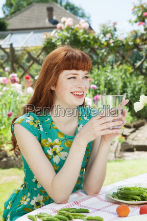 young woman drinking water smiling