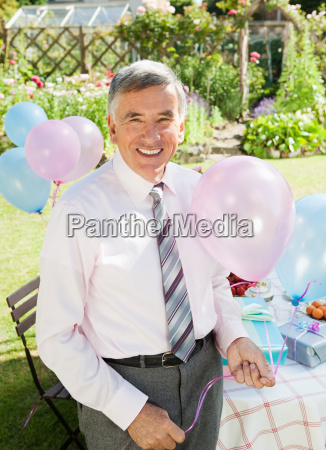 mature man holding balloons