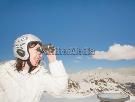 woman with binoculars in snowy mountains