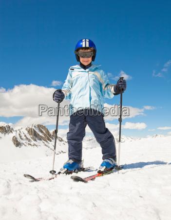 boy skiing in snow mountain backdrop