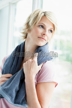 woman with towel looking out window