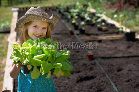 young girl planting vegetables