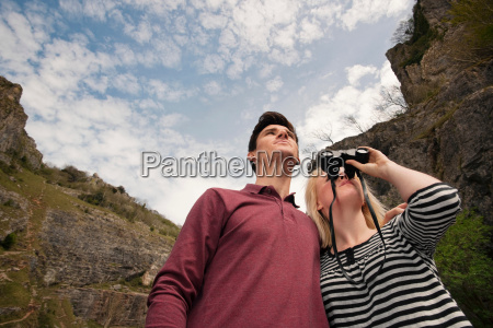 couple looking with binoculars in valley