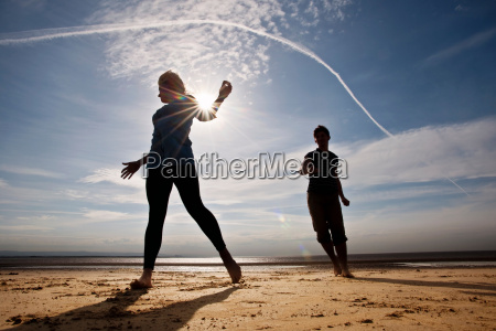 two people running on beach