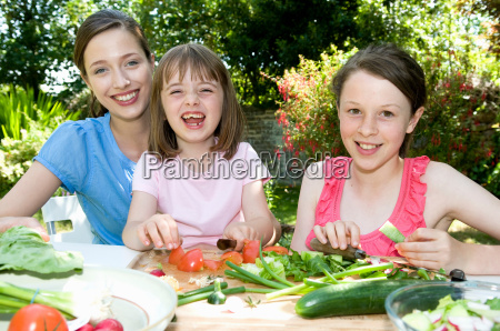 happy mother and daughters prepare food