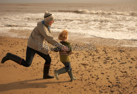 woman running playing with boy on