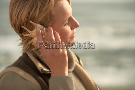 woman by sea listening in seashell