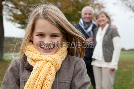 girl and grandparents outdoors in autumn