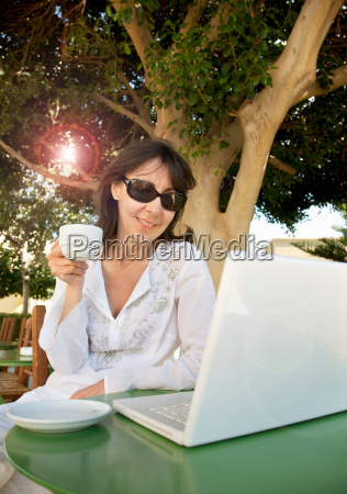 woman with coffee working on laptop