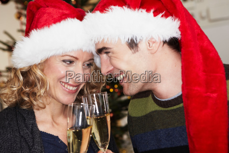 couple with xmas caps clinking glasses