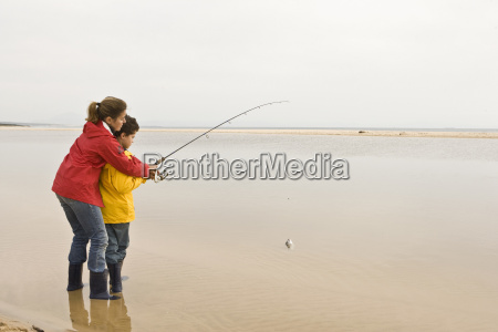 mother teaching son to fish at
