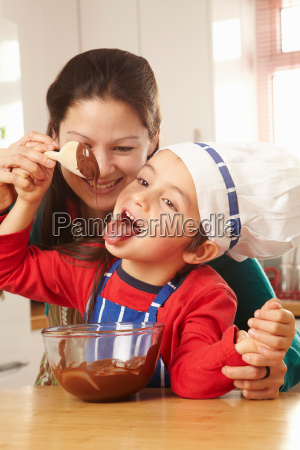 boy licking chocolate off spoon with