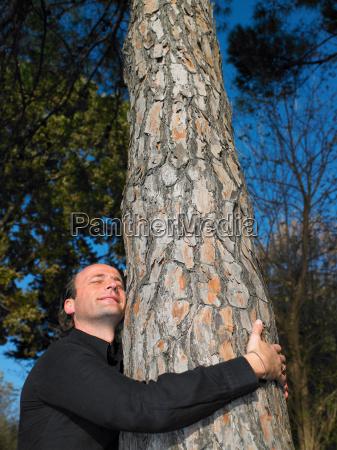 man hugging a tree