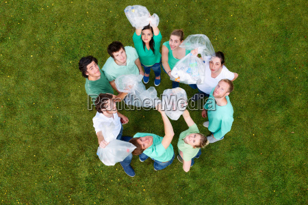 people holding garbage bags on grass
