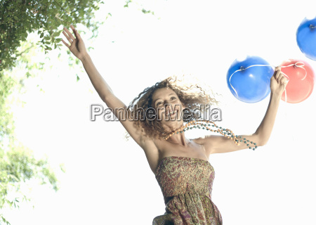 woman with balloons jumping outdoors