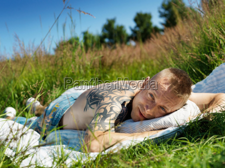 man with large tattoo laying in