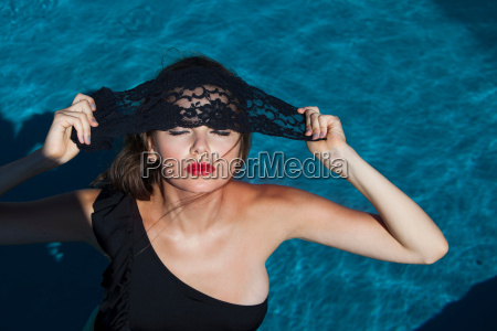 woman posing by swimming pool