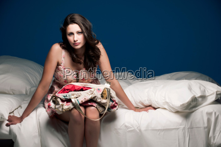teenage girl holding purse on bed