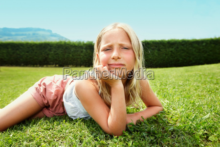 curious girl laying in grass