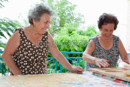 older, women, making, pasta, together - 18163046