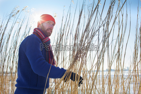 smiling man standing in tall reeds