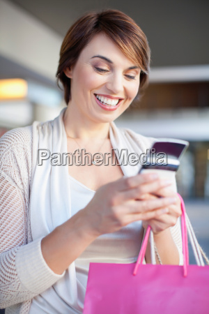 woman using cell phone on city