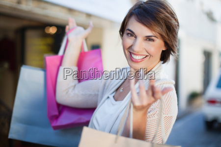 woman carrying shopping bags outdoors