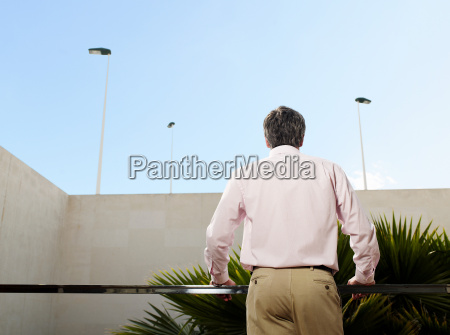 man standing on balcony rear view