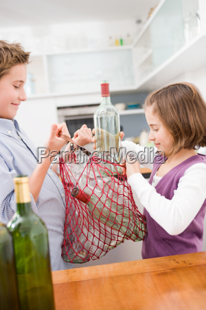 boy and girl recycling empty bottles