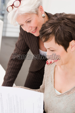 two women studying some papers