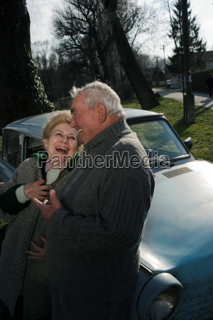 senior couple leaning on car in