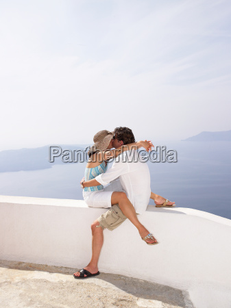 couple kissing on a low wall
