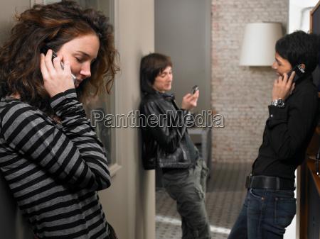 three women using mobiles in corridor