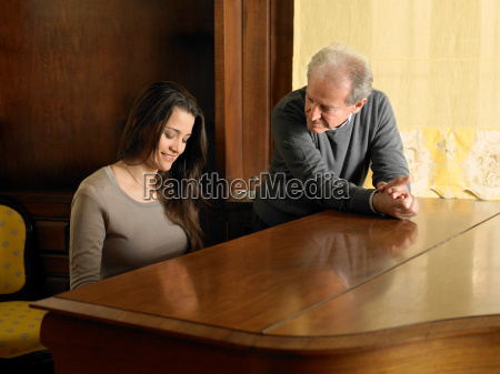 young woman playing grand piano