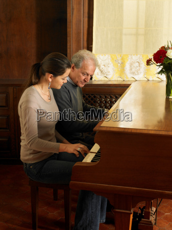 young woman playing piano with man