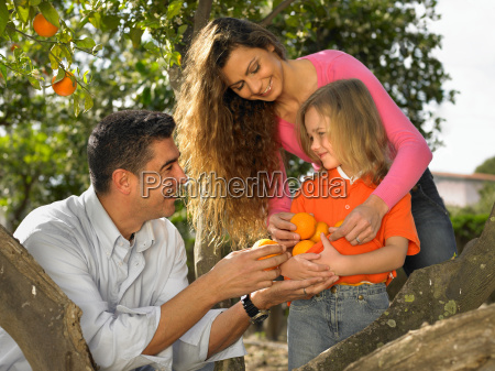 young girl and parents with oranges