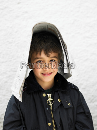 boy outdoors covering head