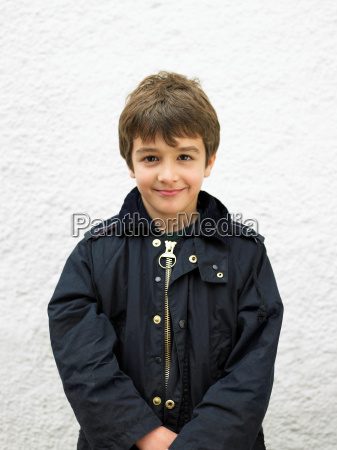 young boy standing by wall