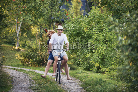 two young men riding bicycle barefoot
